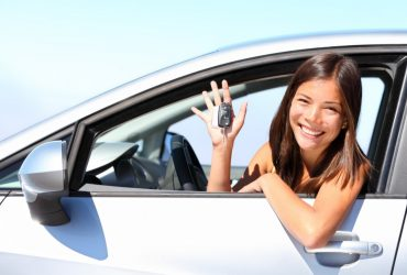 Asian car driver woman smiling showing new car keys and car. Mixed-race Asian and Caucasian girl.; Shutterstock ID 81123025; PO: aol; Job: production; Client: drone